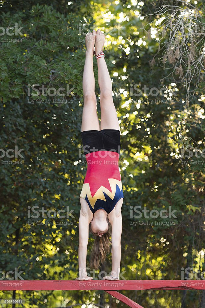 Performing Walkover on Balance Beam. stock photo