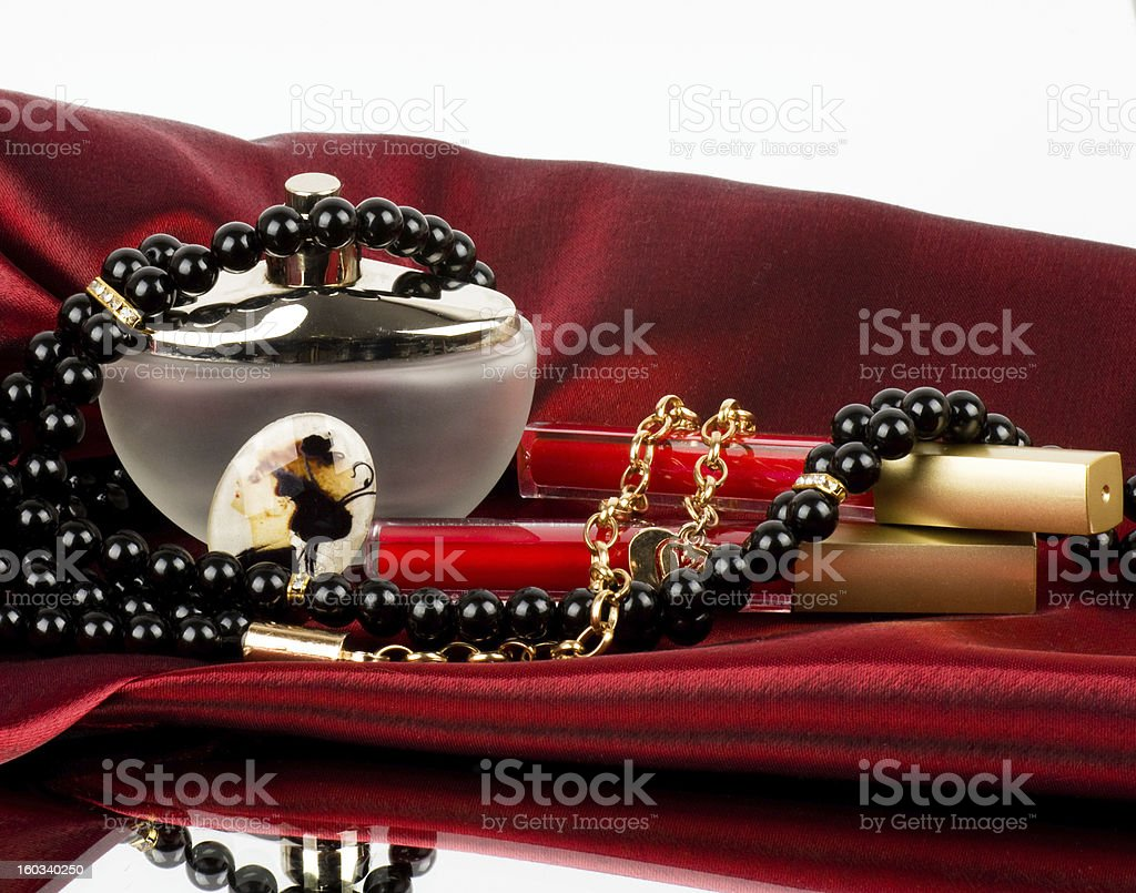 Perfume bottle, red lipstick and pearls beads stock photo