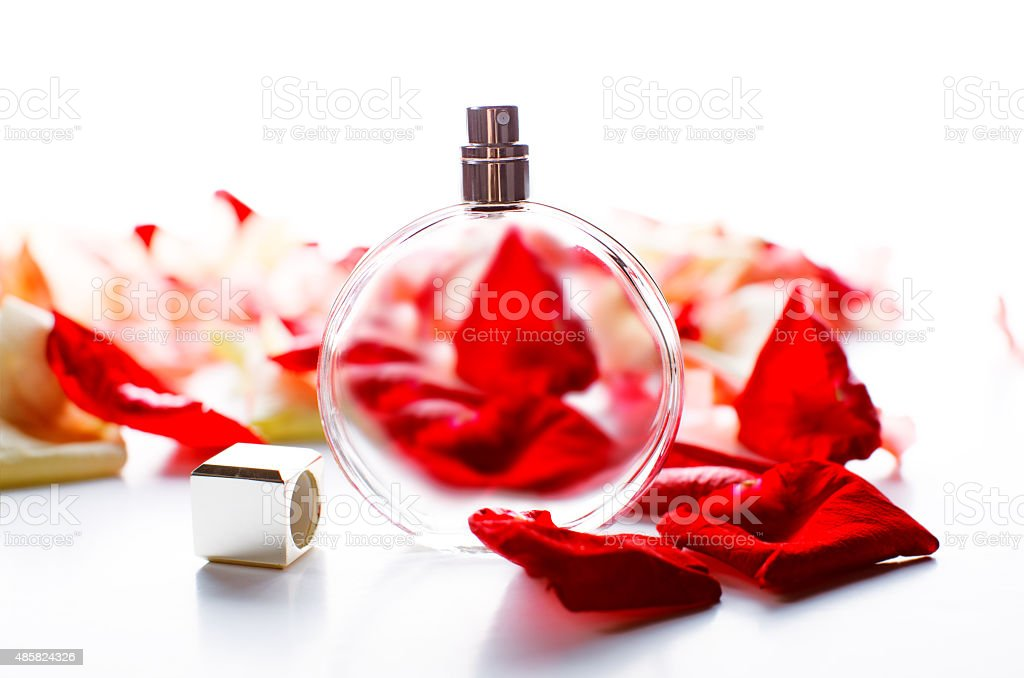 Perfume bottle with petals on table close-up stock photo
