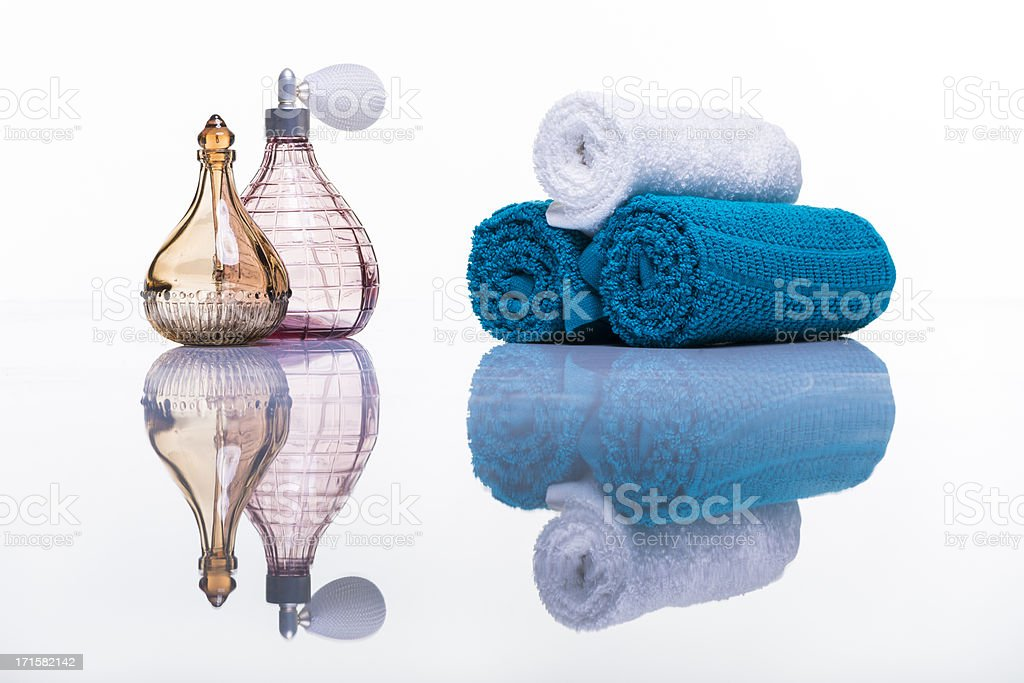 Perfume bottles and towels studio shot on white with reflection royalty-free stock photo