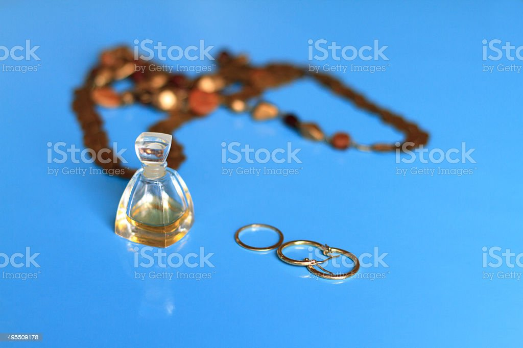 Perfume, Earrings, Ring, Necklace, Blue Background stock photo