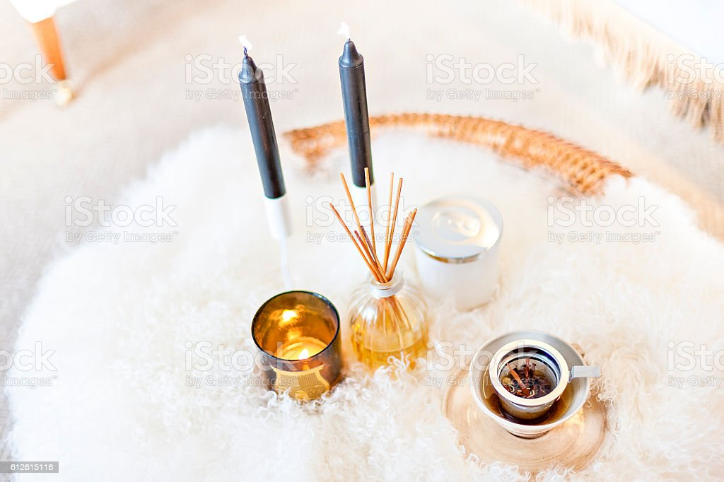 Perfume liquid and sticks in the glass bottles with candles stock photo