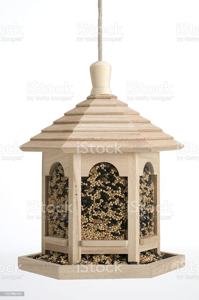 Pergola shaped wooden bird feeder filled with bird seed stock photo