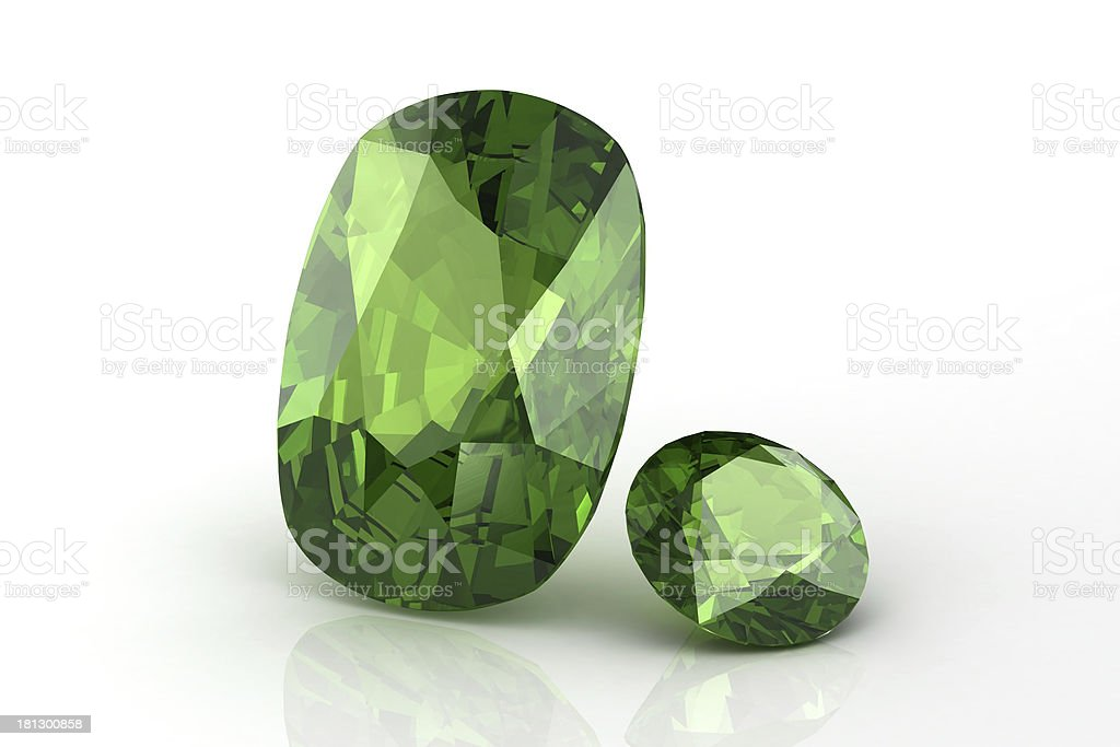 2 peridot jewels on white surface with slight reflection stock photo