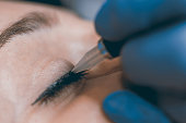 Permanent make up. Cosmetologist applying permanent makeup on eyes.