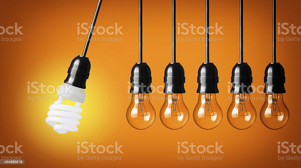 Perpetual motion with light bulbs and energy saver bulb stock photo