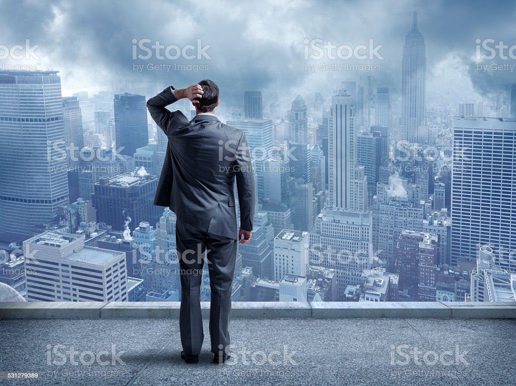 Perplexed Businessman Looking At Cityscape stock photo