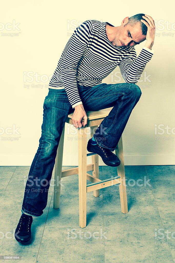perplexed man sitting on stool, holding his head for  problems stock photo