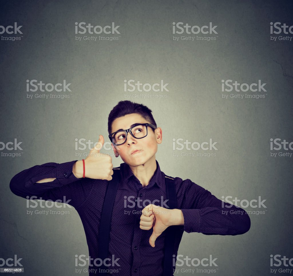 Perplexed man with thumbs down thumbs up gesture looking up stock photo