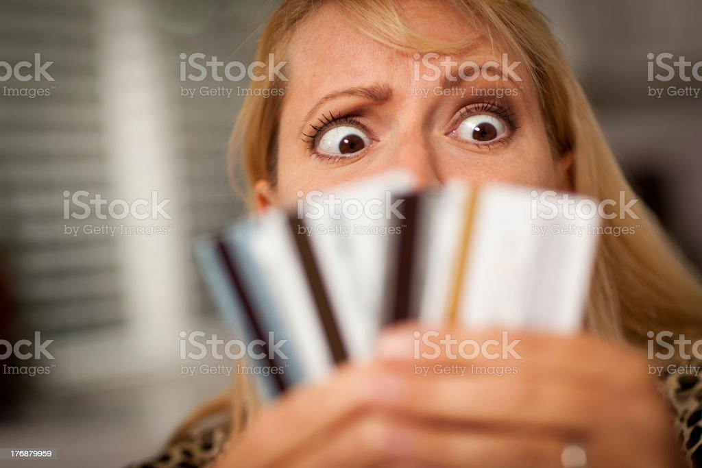 A perplexed woman looking at various credit cards royalty-free stock photo