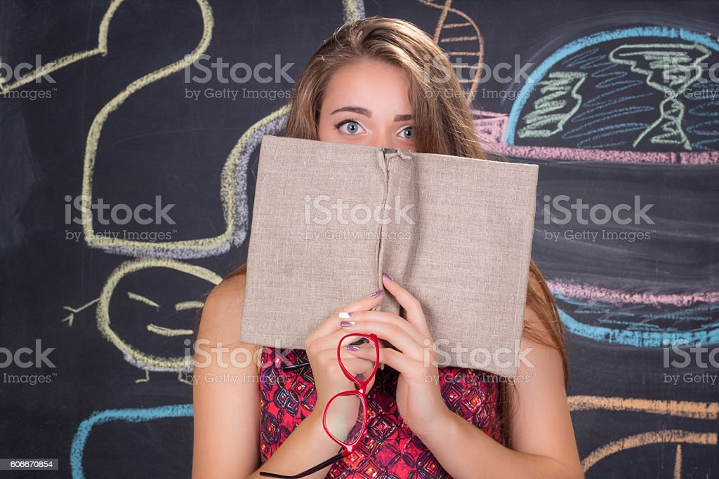 Perplexed young student girl hides behind a book stock photo