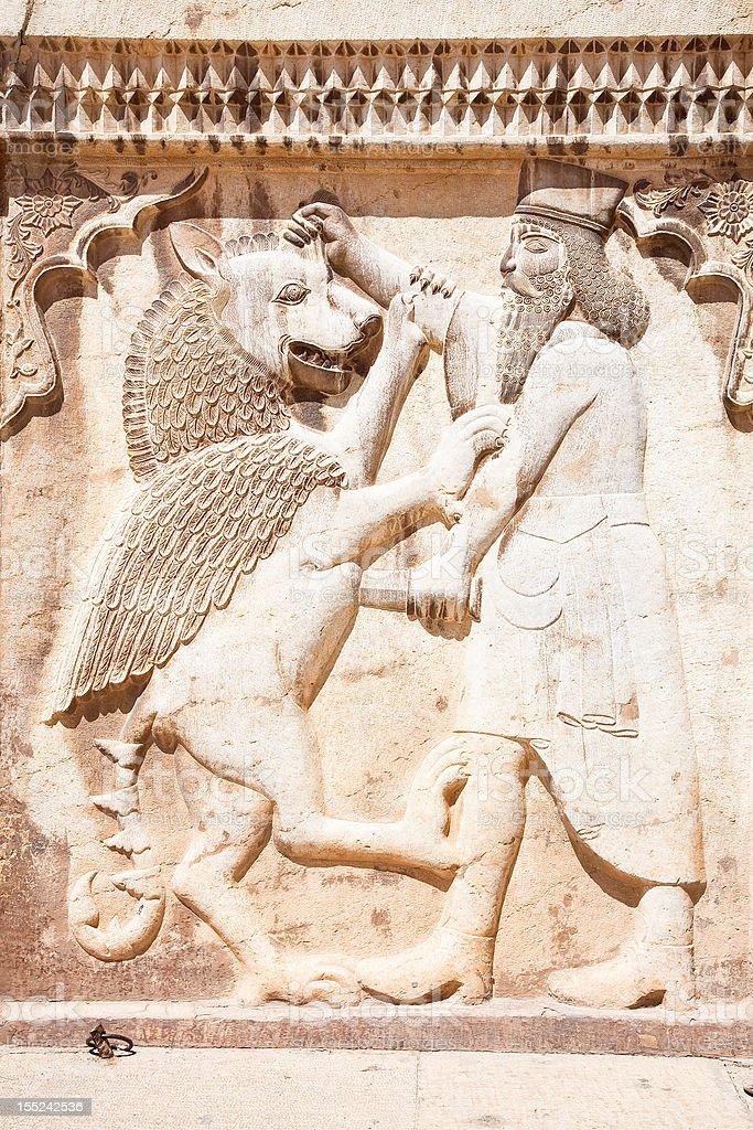 Persian soldier bas-relief killing a bist, stone statue in Shiraz   stock photo