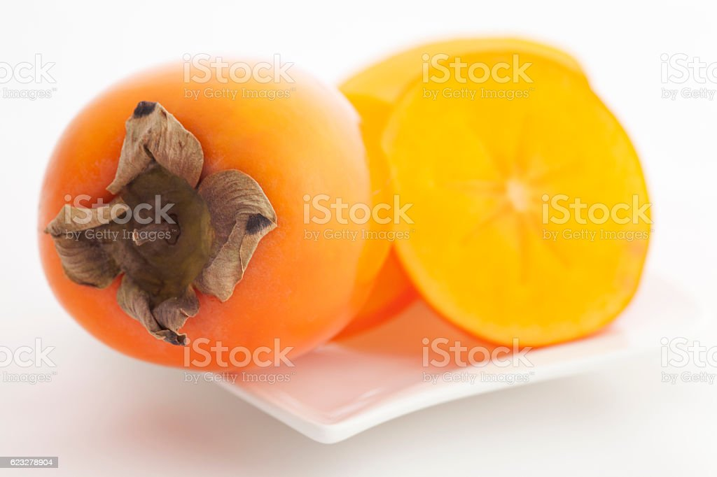 Persimmons on plate stock photo