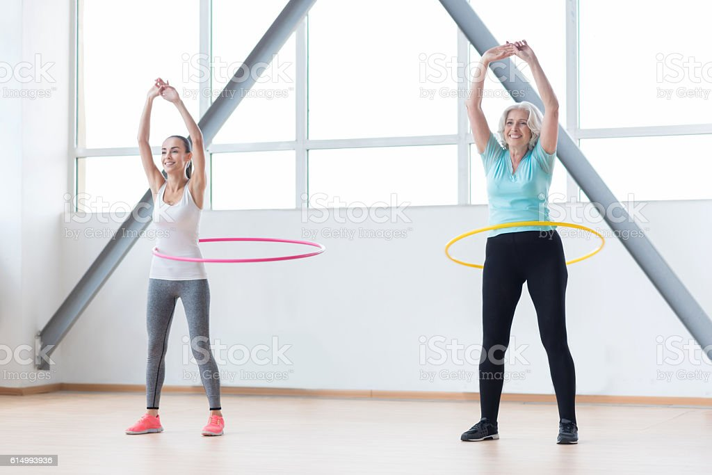 Persistent positive women exercising with hula hoops stock photo