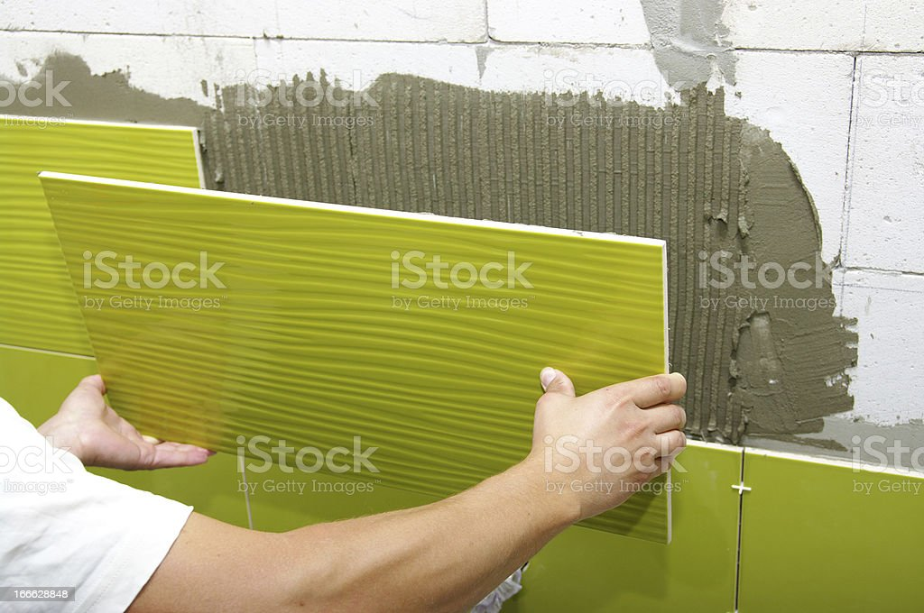 A person adding lime green ceramic tile to a wall royalty-free stock photo