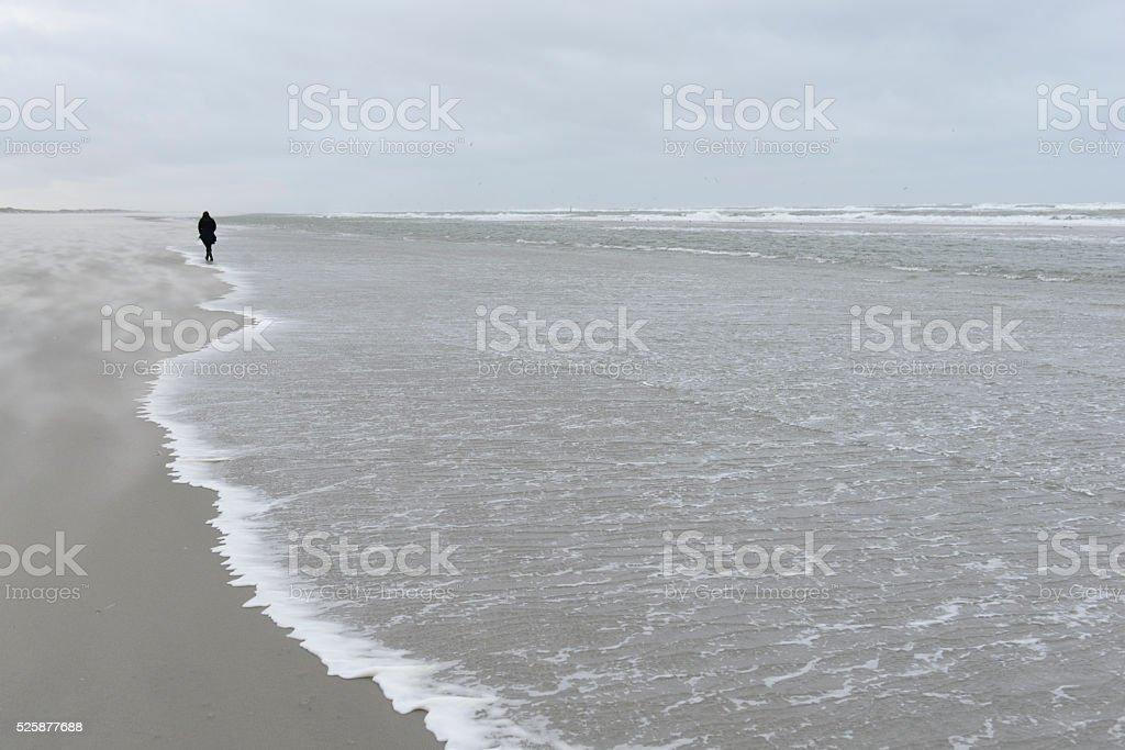 Person alone walking along stormy coastline stock photo