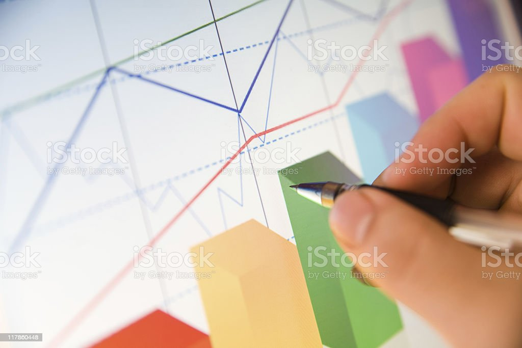 Person analyzing data in colorful line and bar graphs royalty-free stock photo