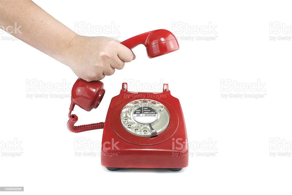 Person answering an old fashion red rotary telephone stock photo