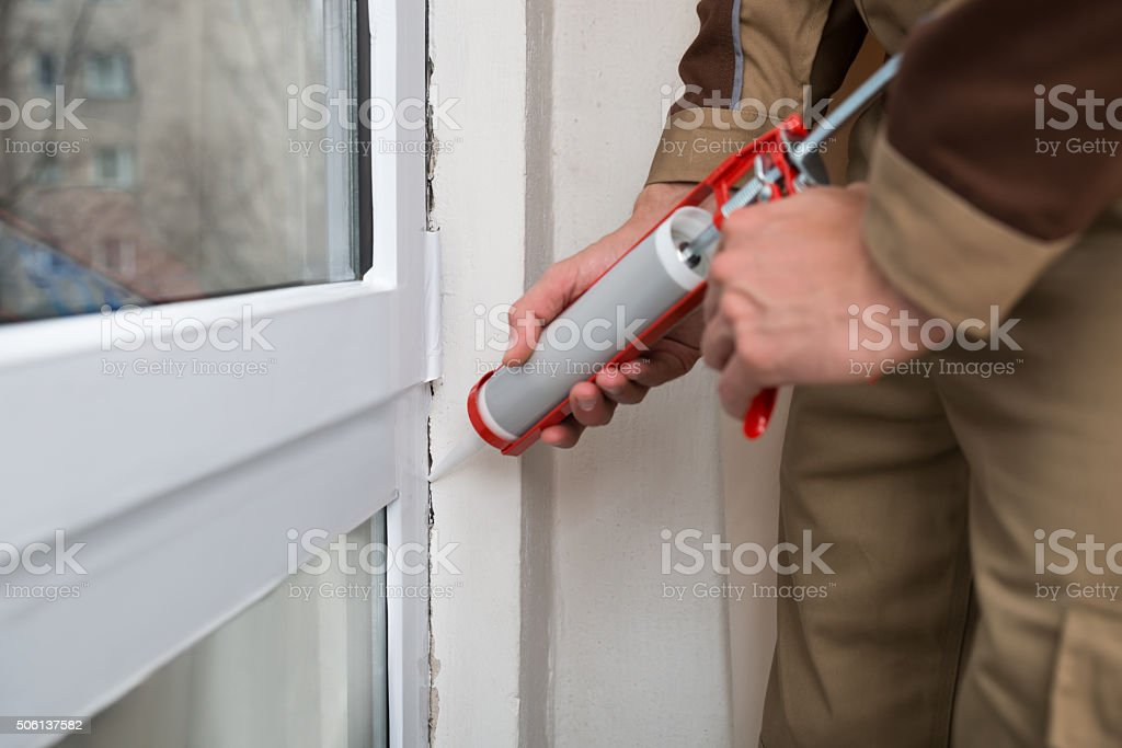 Person Applying Silicone Sealant stock photo