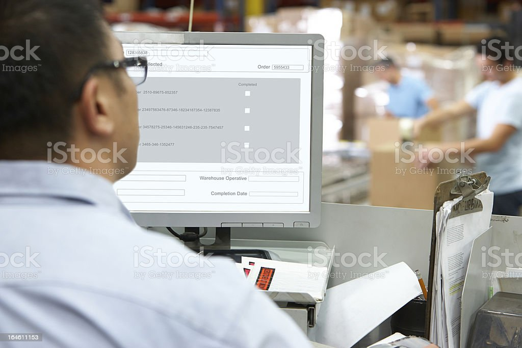 Person At Computer Terminal In Distribution Warehouse stock photo