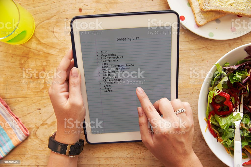 Person At Lunch Looking At List On Digital Tablet stock photo