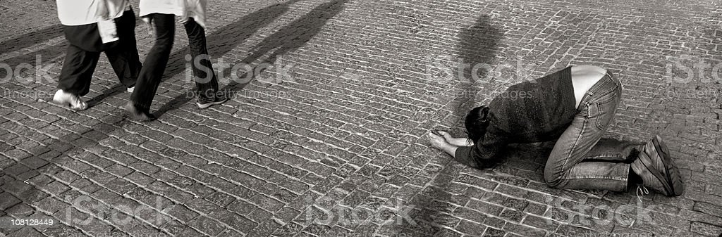 Person Begging as People Walk By royalty-free stock photo