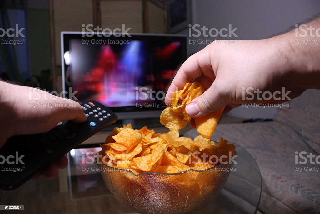Person changing the TV station and reaching for potato chips stock photo