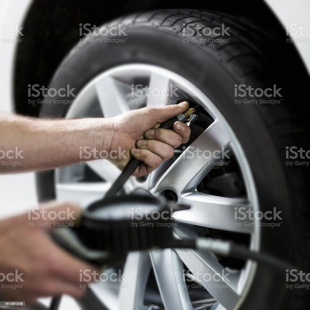 Person checking the tire's pressure royalty-free stock photo