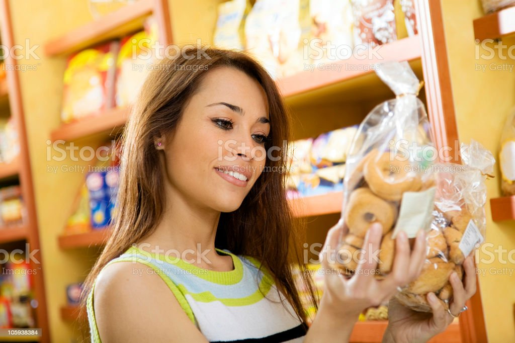 Person choosing between two bags of bagels in store  stock photo