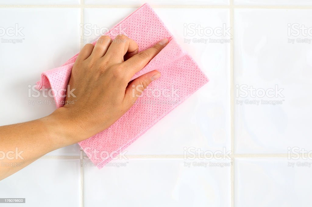 A person cleaning the surface of a kitchen countertop  royalty-free stock photo