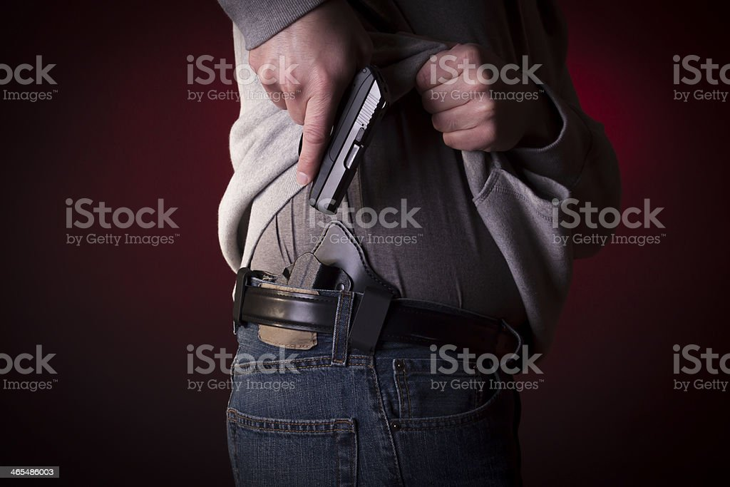 A person concealing their pistol on their hip stock photo
