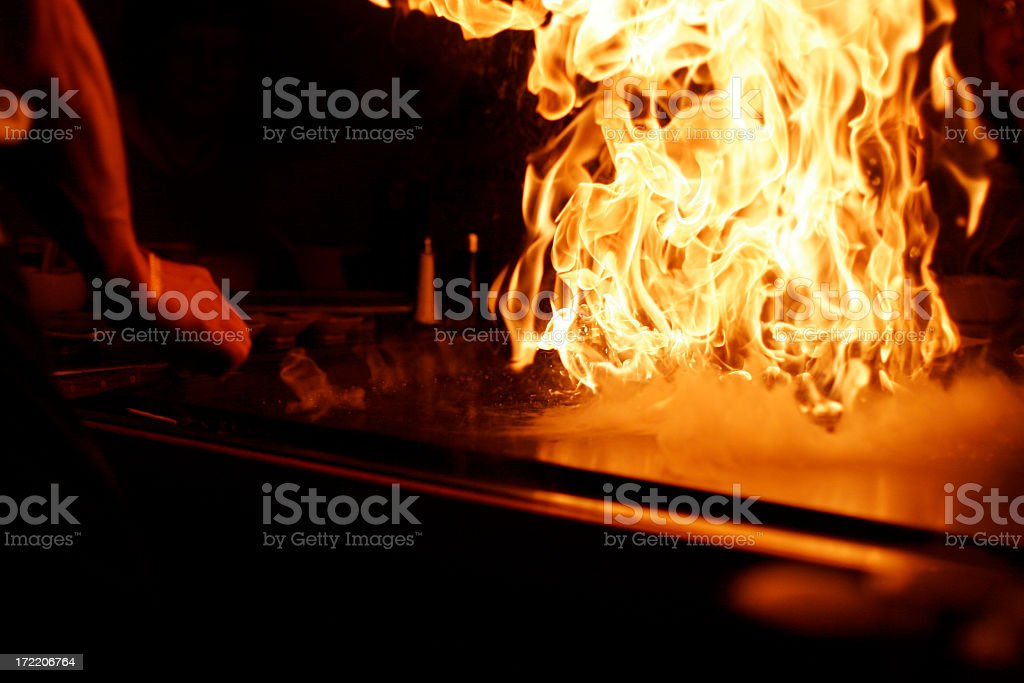 A person cooking with a high fire flame stock photo