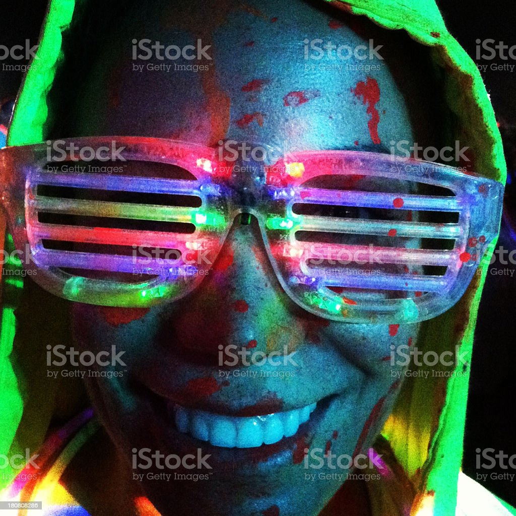 A person covered in red paint wearing neon glasses royalty-free stock photo