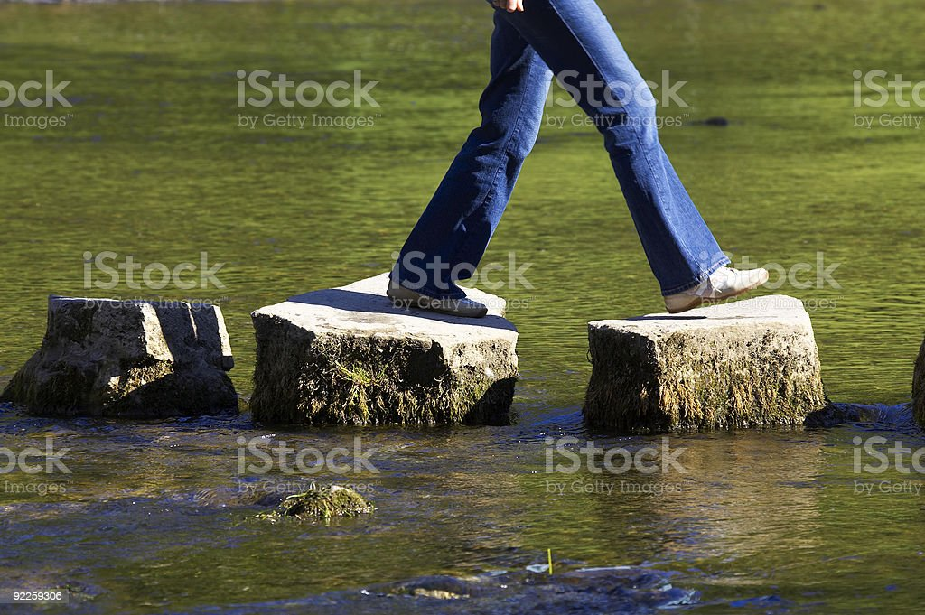 A person crossing three stepping stones on a river stock photo