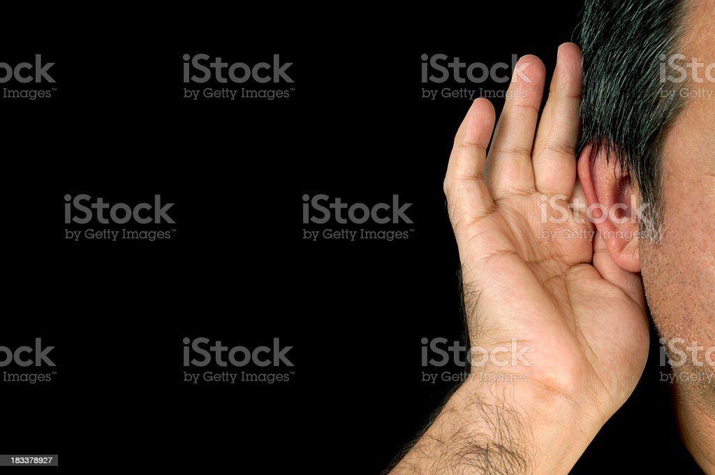 Person cupping right ear to hear sound isolated on black royalty-free stock photo
