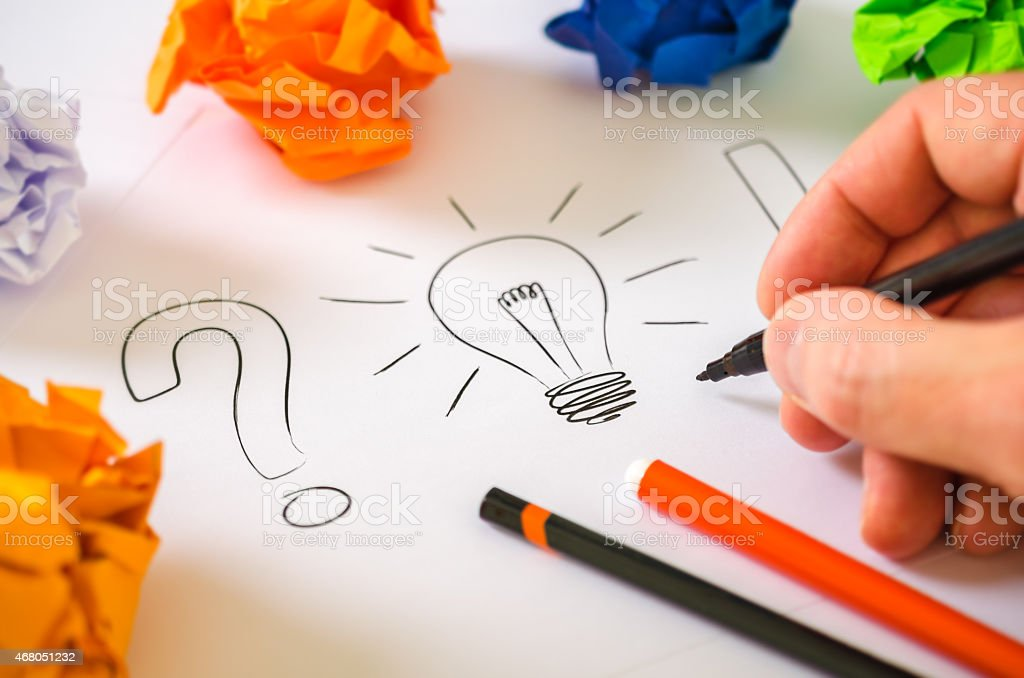 Person drawing a lightbulb and punctuation icons stock photo