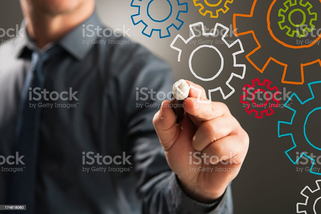 Person drawing colourful cogs on presentation screen royalty-free stock photo