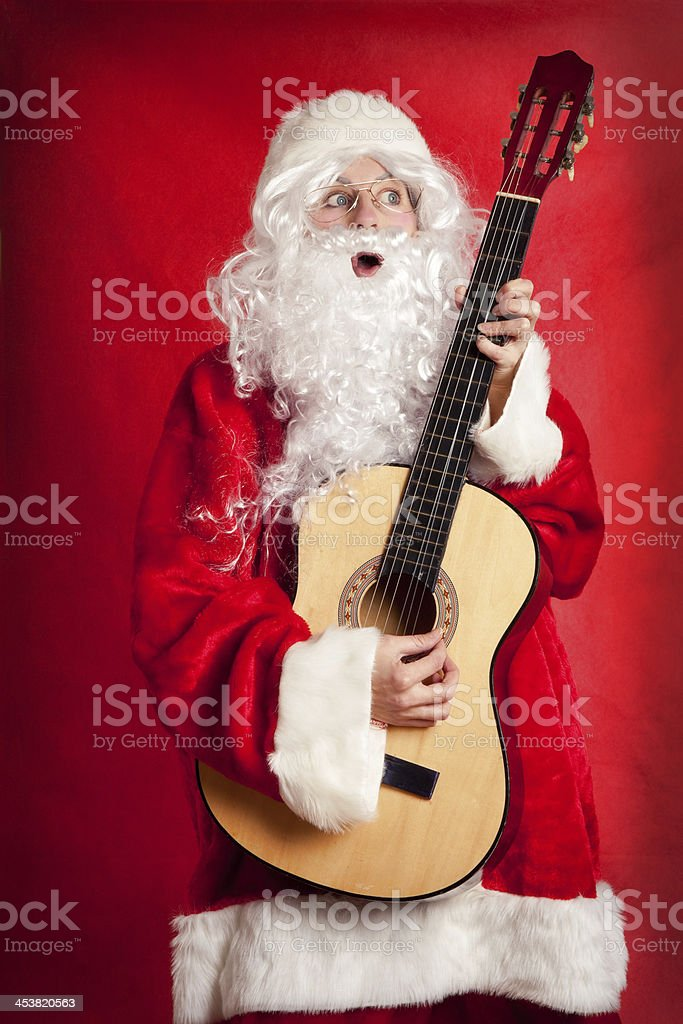 Person Dressed As Santa Playing Acoustic Guitar and Singing stock photo