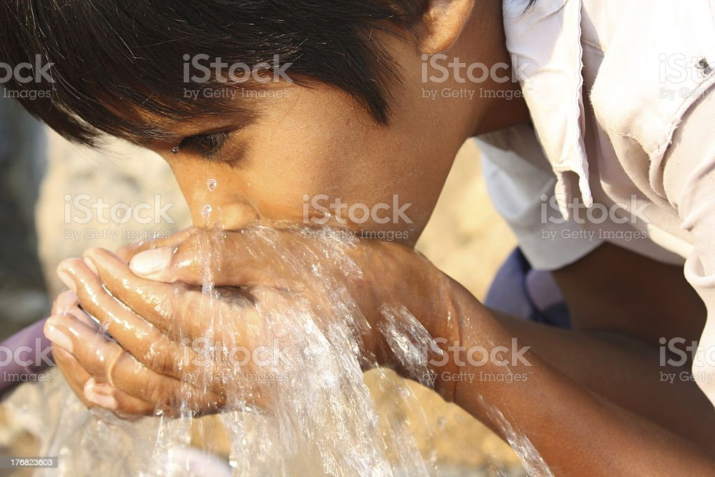 A person drinking water with their hands stock photo