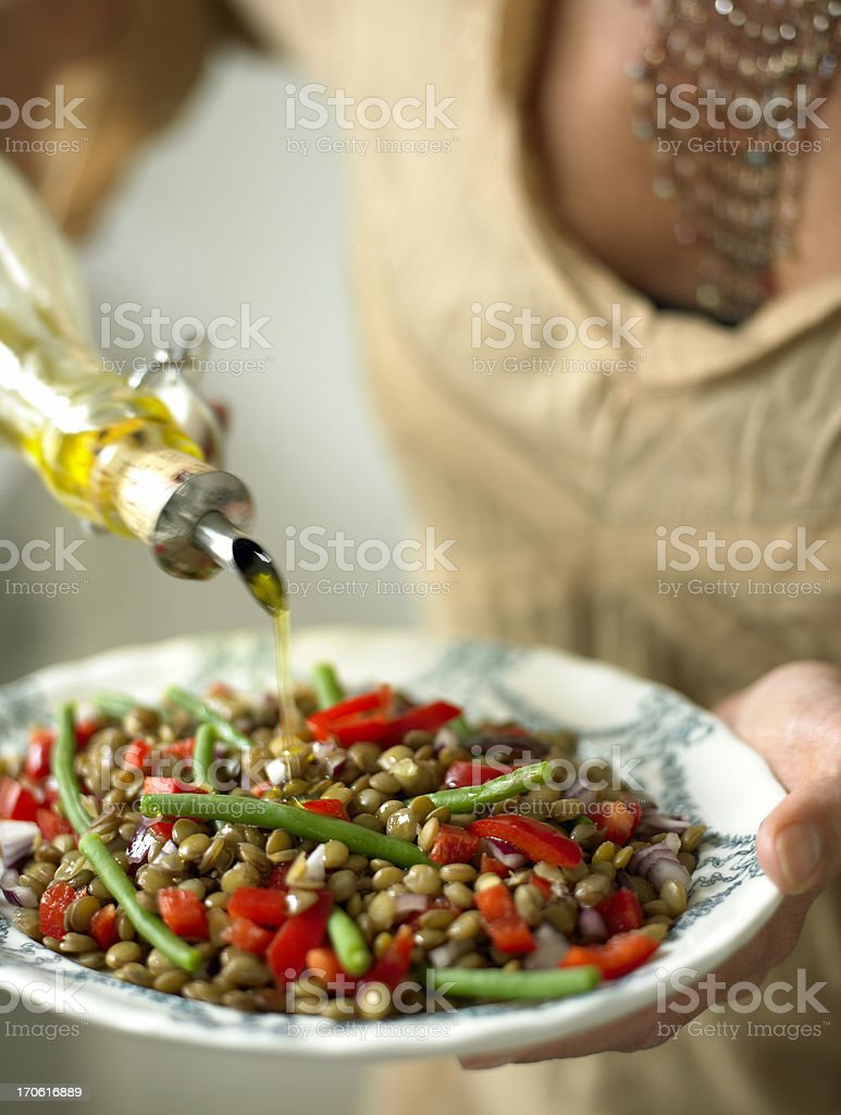 Person eating a lentil salad pouring olive oil on top royalty-free stock photo