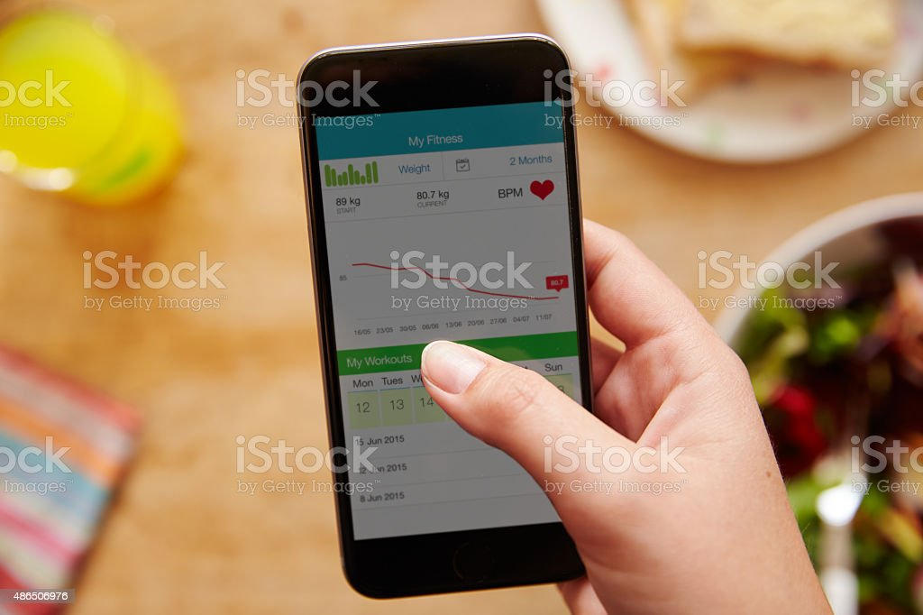 Person Eating Lunch Looking At Fitness App On Mobile Phone stock photo