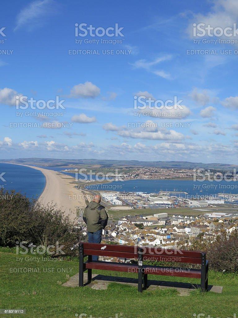 Person enjoying view over Chesil Beach stock photo