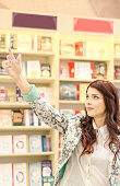 Person enjoys buying books at the library or bookstore.