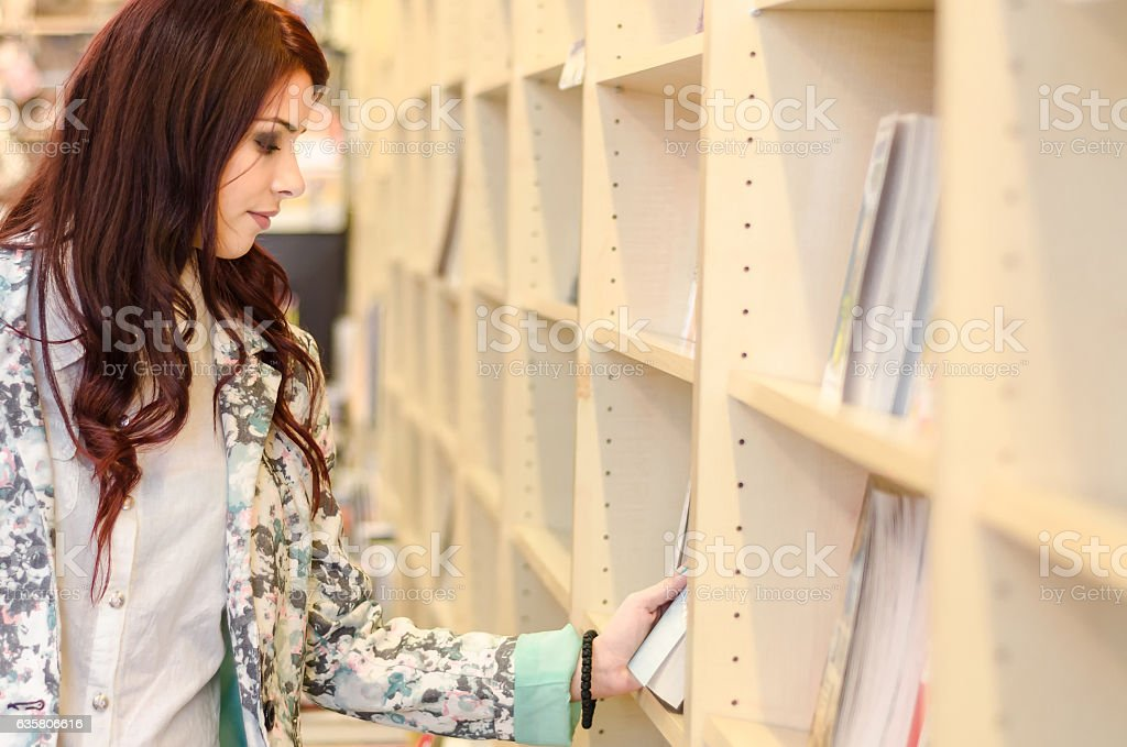 Person enjoys buying books at the library or bookstore. stock photo