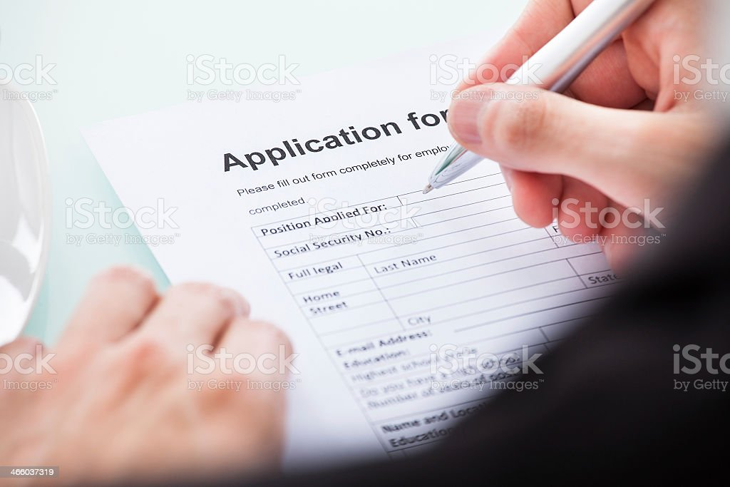 Person filling out a form by hand stock photo