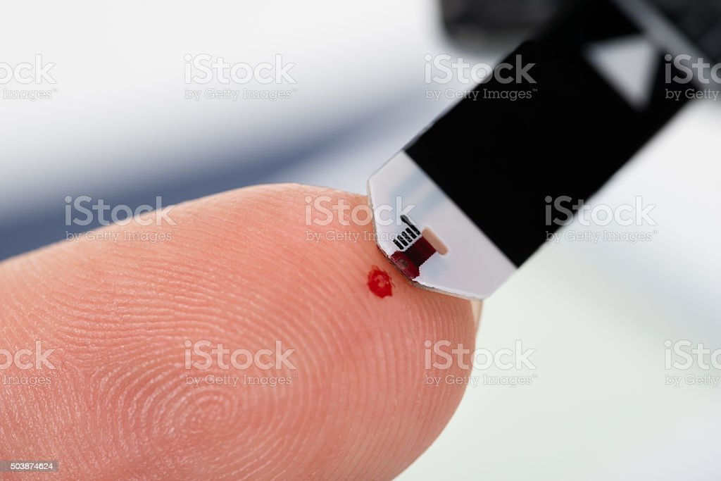 Person Finger With A Glucometer stock photo