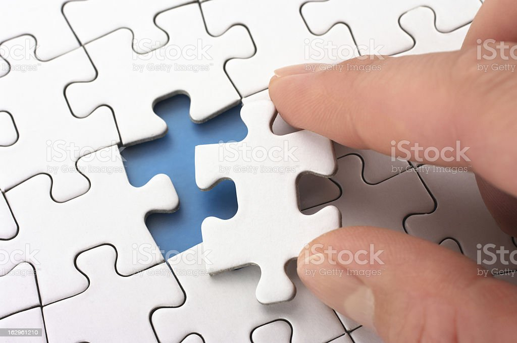 Person fitting the last puzzle piece. royalty-free stock photo
