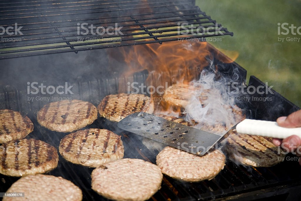 Person Flipping Burgers During BBQ royalty-free stock photo
