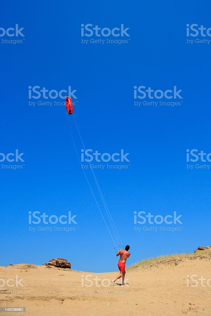 Person flying a kite at the beach stock photo