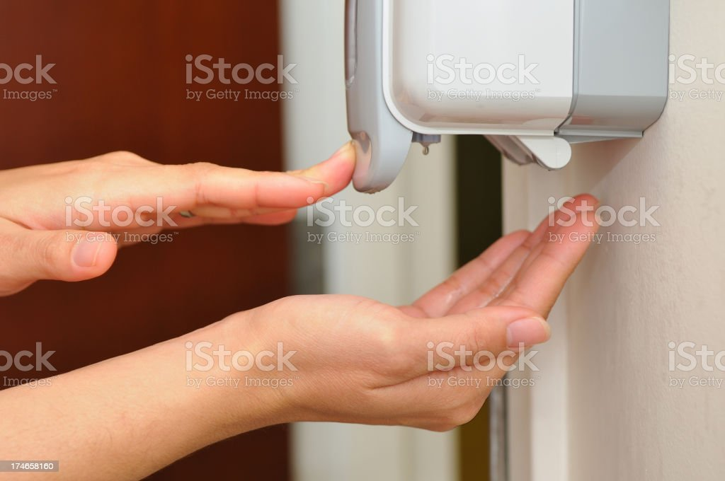 Person getting soap from a hand dispenser stock photo
